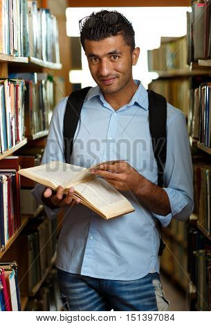 Young arab student reading book between the shelves in the library