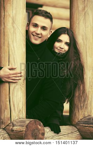 Happy young fashion couple standing on the porch of wooden house