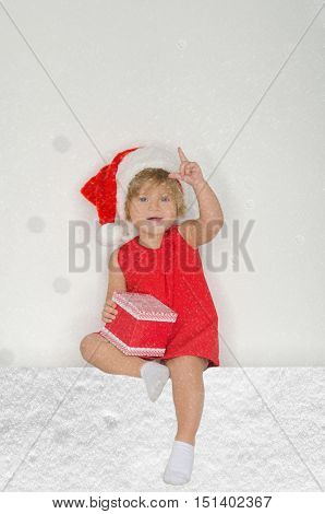 little girl in Santa suit with snowflakes with gift on gray background