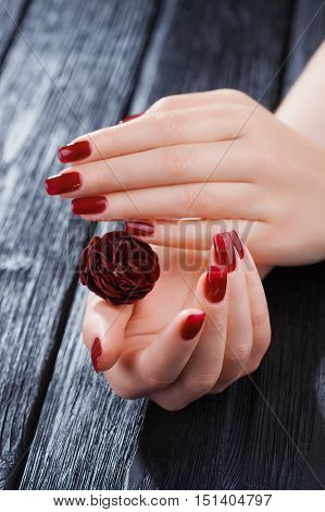 Red Manicure On The Black Wooden Table