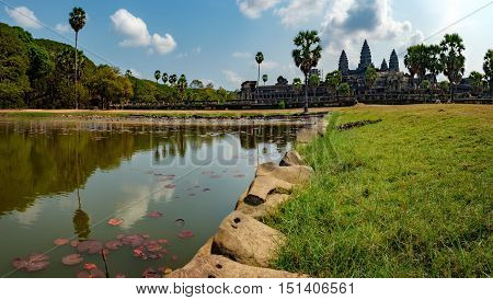 Ancient ruins of temple complex Angkor Wat seen across the pond with lilies Siem Reap Cambodia.