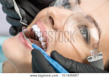 Gorgeous girl in protective glasses. Her teeth are checking with the help of a dental bur and a dental mirror. Macro photo. Horizontal.