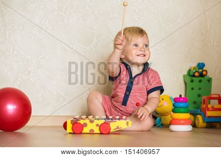 Portrait of a beautiful baby boy on the floor with toys. 15 year-old child playing with educational cup toys at home. Little blond kid with blue eyes is playing with toy at home indoors