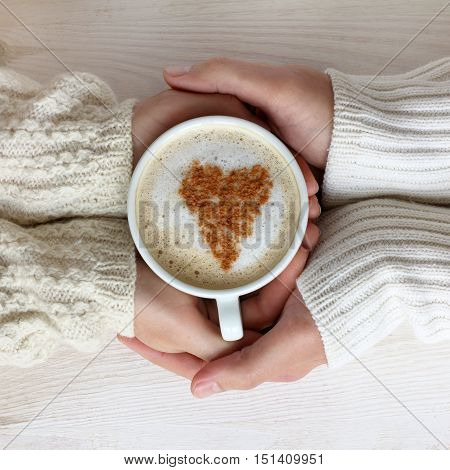 cup with a frothy cappuccino and heart symbol in the hands two persons / breakfast with a favorite coffee