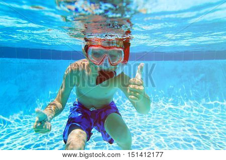 happy little boy swimming underwater with thumbs up, kids sport