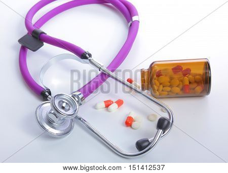 medical stethoscope with pills isolated on white background.