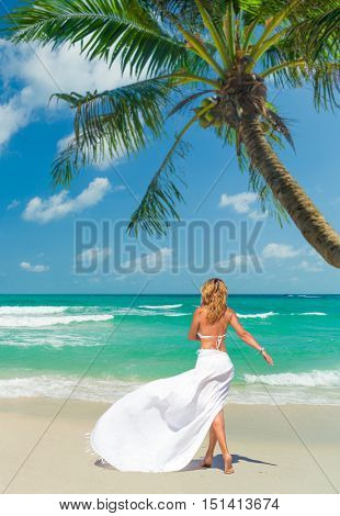 Young woman walking on idyllic tropical  beach