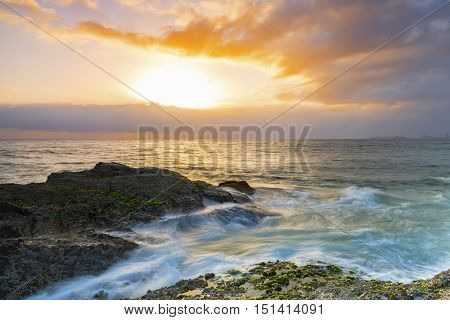 Ocean rushing over the end of Currumbin Rock Gold Coast, as the sunrises over the ocean.