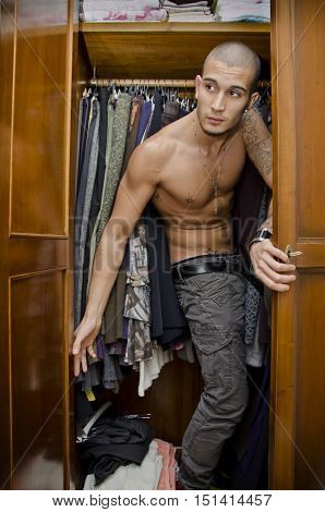 Handsome shirtless young male lover hiding from his woman's husband inside closet