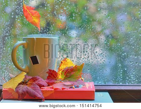 Tea cup at the window with  leaves and drops after rain in autumn