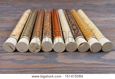 Set Of Spices And Condiments In Glass Tubes On A Wooden Background