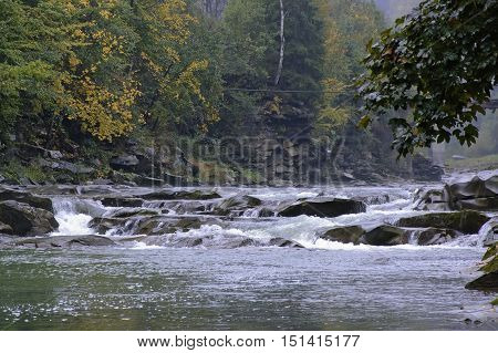 The bank of the Prut river in Carpathians at cloudy autumn day