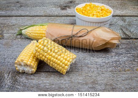 Ears Of Corn Wrapped In Paper, Half The Corn And Grain In A Bowl On A Rustic Wooden Background