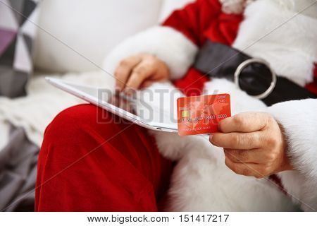 Santa Claus with credit card and tablet on couch at home