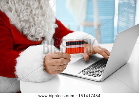 Santa Claus with credit card and laptop at home, closeup