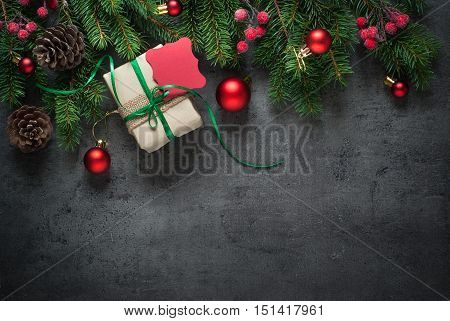 Christmas decorations and fir tree branch on dark table. Top view with copy space