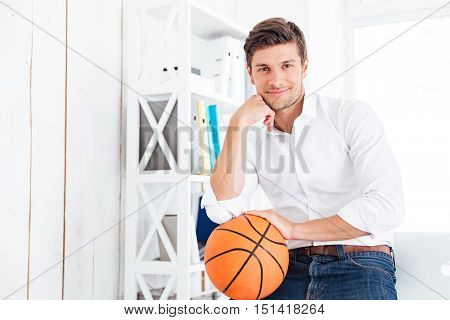 Handsome businessman sitting at the table with basket ball in office