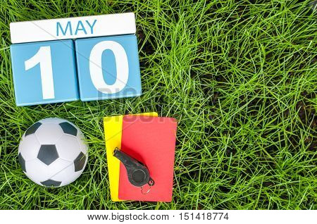 May 10th. Day 10 of month, calendar on football green grass background. Spring time, empty space for text.