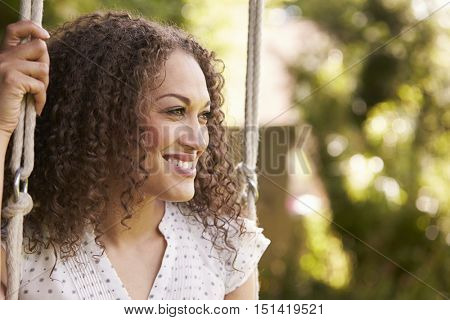 Head And Shoulders Shot Of Mid Adult Woman Sitting On Swing