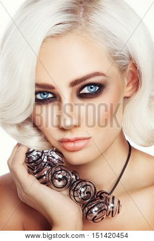 Close-up portrait of young beautiful woman with stylish smoky eye make-up and fancy glass necklace