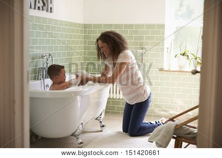 Mother And Son Having Fun At Bath Time Together