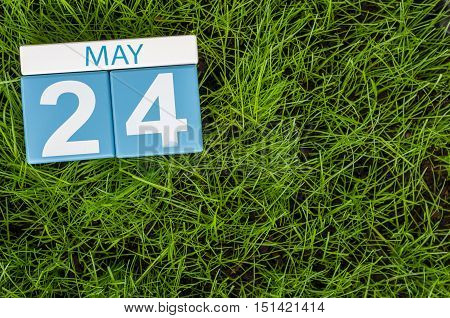May 24th. Day 24 of month, calendar on football green grass background. Spring time, empty space for text.