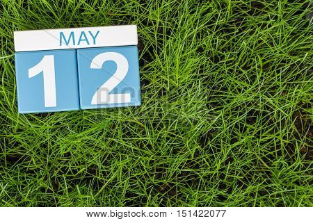 May 12th. Day 12 of month, wooden color calendar on football green grass background. Spring time, empty space for text.
