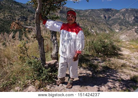 Creel Chihuahua Mexico - October 10 2014: Indigenous Tarahumara man takes rest under the shade of the tree wears traditional tribal outfit in Copper Canyons Chihuahua Mexico on October 10 2014