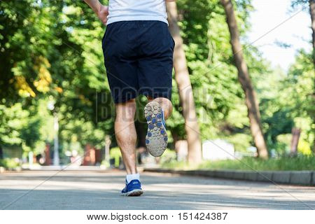 Unfocused man legs running on the asphalt with the sky in the background