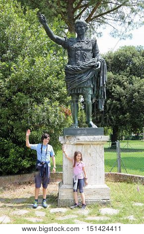 bronze statue of the emperor Caesar Augustus with two young tourists