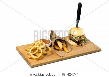 Big hamburger, steak fries and onion rings on a wooden platter