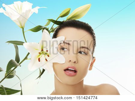 Woman with healthy skin and lily flower
