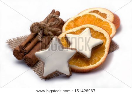 Cinnamon stars with orange slices and cinnamon sticks isolated on white