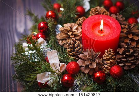 Red candle in a wreath of pine branches with Christmas balls on a wooden background