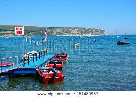SWANAGE, UNITED KINGDOM - JULY 19, 2016 - Boats moored at a small jetty with cliffs to the rear Swanage Dorset England UK Western Europe, July 19, 2016.