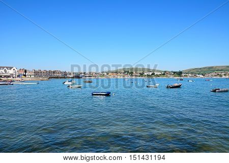 SWANAGE, UNITED KINGDOM - JULY 19, 2016 - View of boats moored in the bay and the beach and town to the rear Swanage Dorset England UK Western Europe, July 19, 2016.