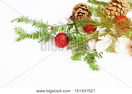 Red Christmas balls fir branches and cones on a white background