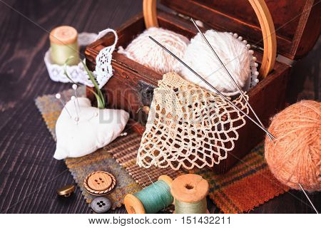 Spool of thread a thimble and a box with needlework on a wooden table close-up