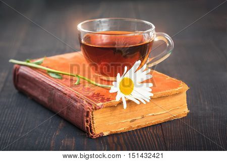 Cup of tea chamomile and a book on the wooden table