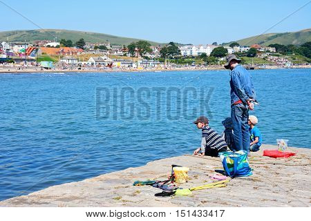 SWANAGE, UNITED KINGDOM - JULY 19, 2016 - Man with children on the harbour looking at the view with the town and beach to the rear Swanage Dorset England UK Western Europe, July 19, 2016.