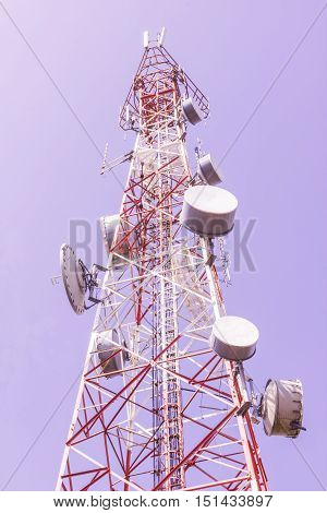 Telecommunication tower with a lot of equipments against blue sky background