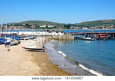 SWANAGE, UNITED KINGDOM - JULY 19, 2016 - View along the beach towards the pier and town Swanage Dorset England UK Western Europe, July 9, 2016.