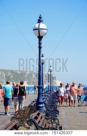 SWANAGE, UNITED KINGDOM - JULY 19, 2016 - Tourists along the Victorian pier with views towards the cliffs Swanage Dorset England UK Western Europe, July 19, 2016.