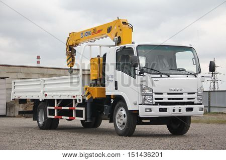 White Isuzu Flatbed Truck With Yellow Crane Arm Is In The Parking Lot - Russia, Moscow, 30 September