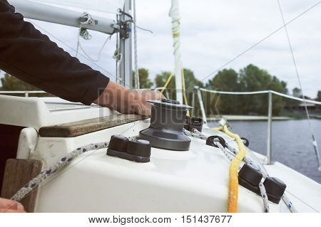 Yacht mans hands holding rope on sailing boat