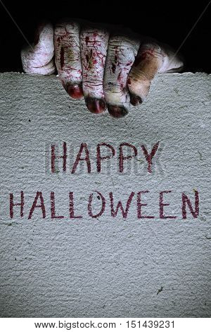 closeup of the scary hand of an undead man holding a signboard with the text happy halloween written in it