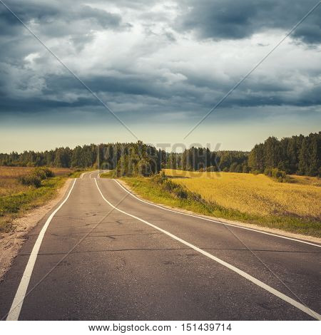 Rural Highway Under Stormy Cloudy Sky