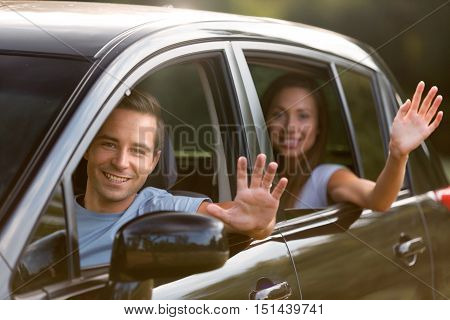 Portrait of a Couple Waving Hands out of the Window of Car
