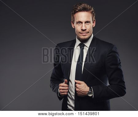 Handsome young businessman in a black suit holding his jacket lapels standing against a gray background