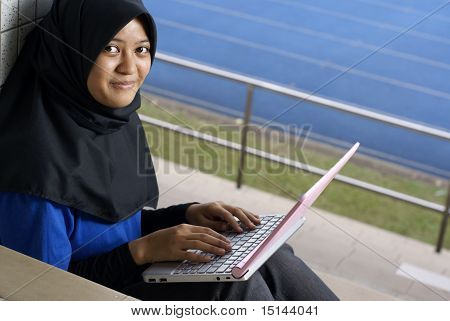 Smiling malay girl with laptop